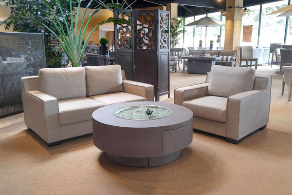 Transitional loveseat and club chair, upholstered with Sunbrella fabric, with round faux-concrete fire pit.